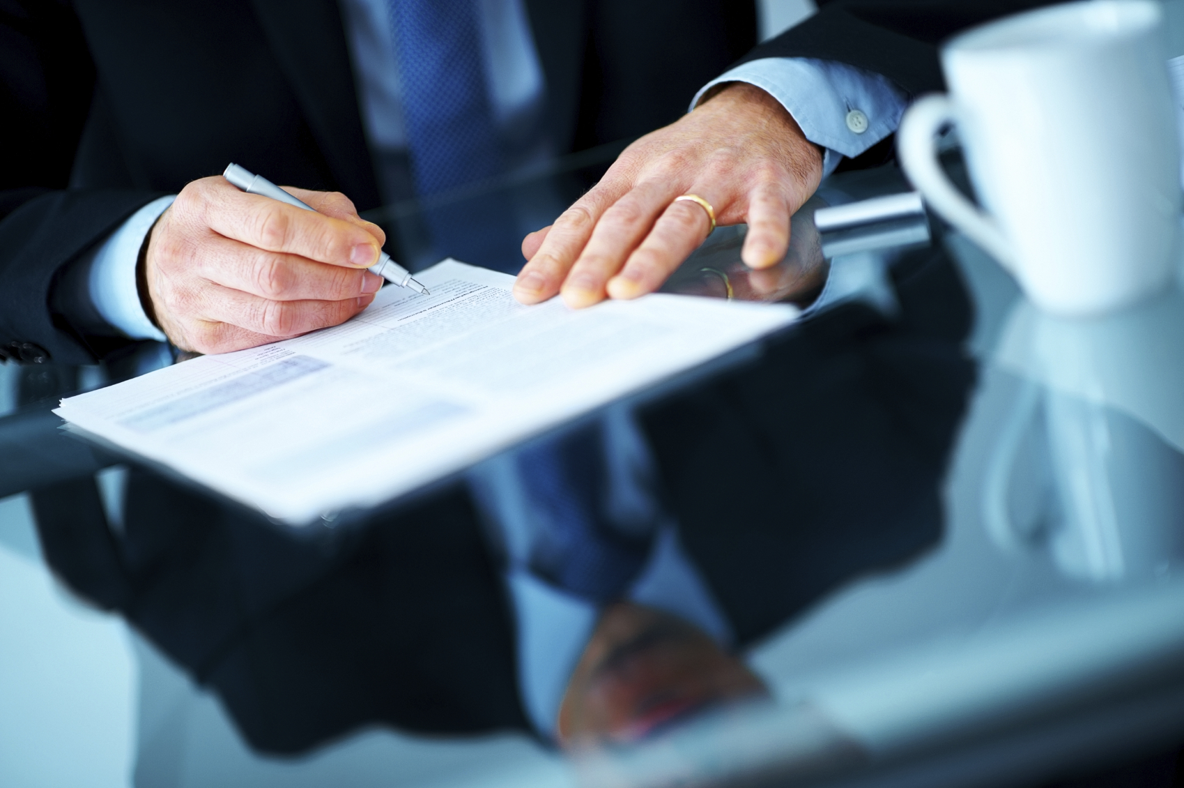 Cropped image of a businessman hands signing a contract or document at a desk